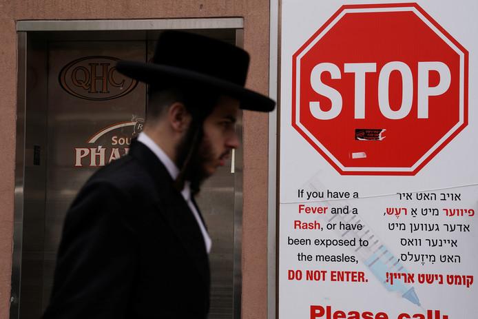 Een Joodse man loopt langs een waarschuwingsbord voor de mazelen.