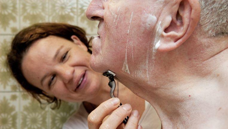 Een medewerkster van Evita Zorg helpt een oudere man bij het scheren. Beeld anp