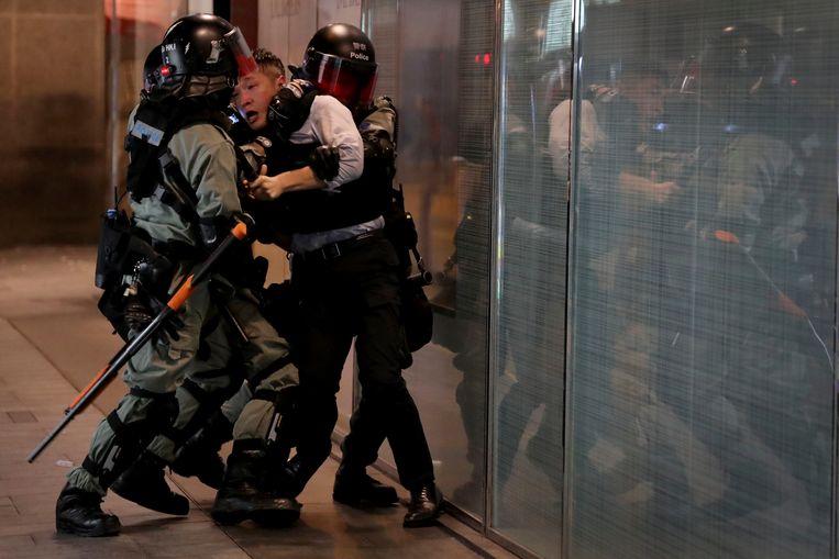 Arrestatie van een man in Central, het zakendistrict van Hongkong waar demonstranten wegen hadden geblokkeerd.  Beeld AP