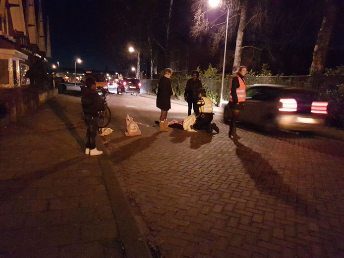 Omstanders en een agent ontfermen zich over het slachtoffer.