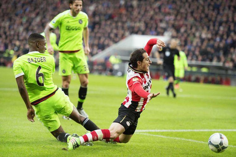 Maart 2016. Riechedly Bazoer van Ajax stopt de PSV-er Andrés Guardado af. Beeld anp