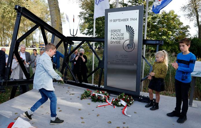 Seppe Maas (links) legt namens zijn familie bloemen bij het Gdyniamonument. Behalve Seppe, onthulden ook Floor Vinke en Lars de Vetter het monument.