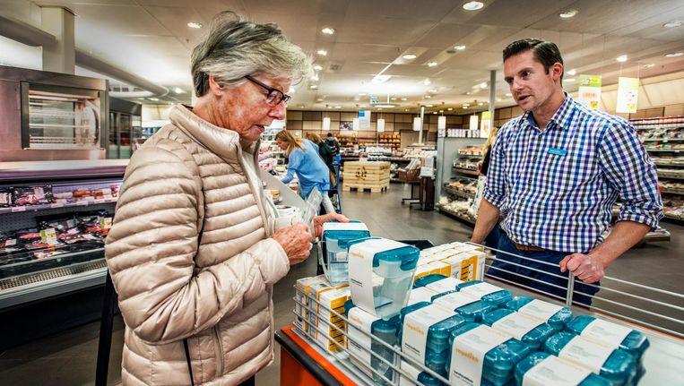 Een klant bij de Albert Heijn in Breukelen komt een van de laatste vershouddoosjes halen met een volle spaarkaart. Beeld Raymond Rutting / de Volkskrant