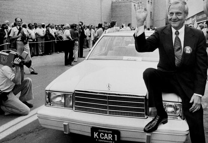 Een foto uit 1980: Iacocca op de motorkap van de K Car Number One van Chrysler.