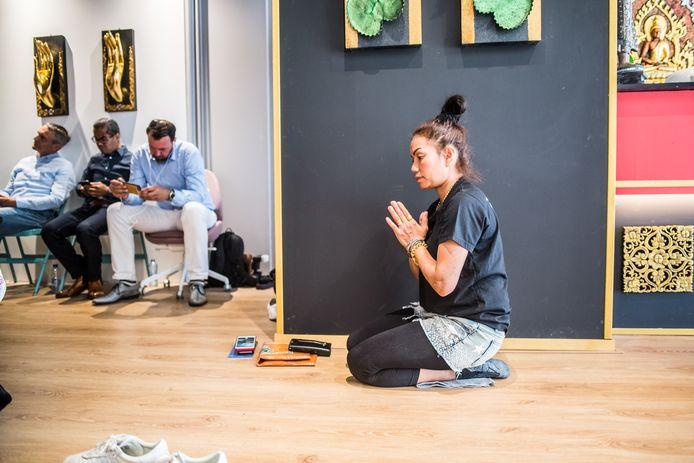 Gemoedelijkheid alom: een Thaise verzonken in gebed, terwijl de Nederlandse gasten op de achtergrond de net genomen foto's op hun telefoons bekijken.