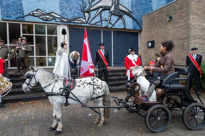 Pastoor Hans Hermans hanteert de wijwaterkwast bij het inzegenen van de deelnemers aan de Sint Hubertusrit.