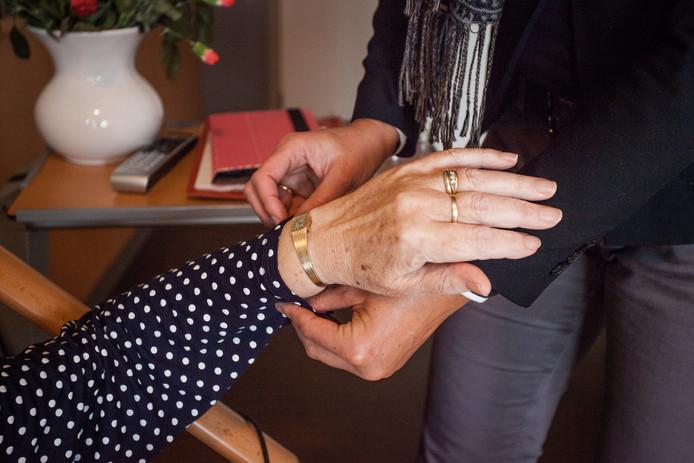 Een oudere mevrouw krijgt hulp van een thuiszorgmedewerker bij het aankleden