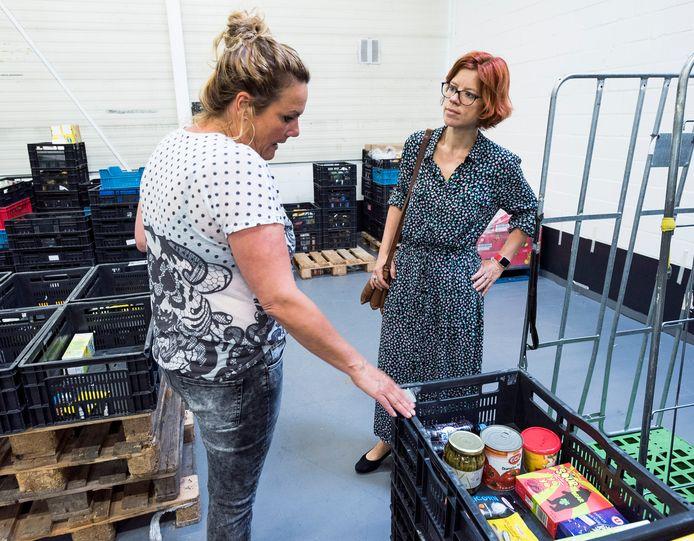 Wethouder Linda Voortman (r) op werkbezoek bij het distributiecentrum van de voedselbank Utrecht in de wijk Overvecht.