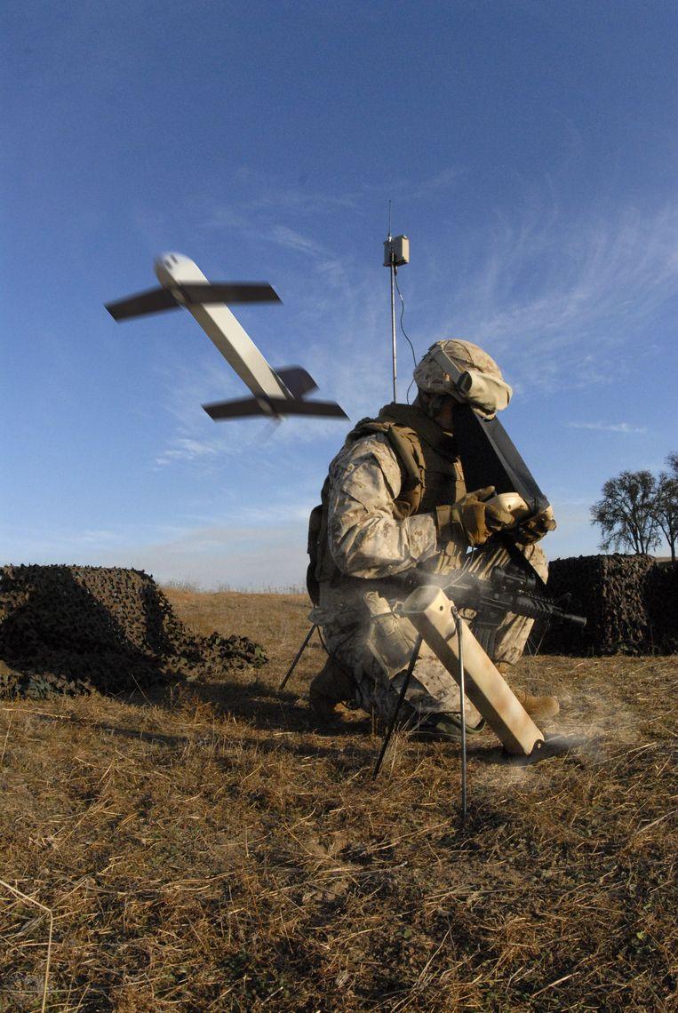 Een Amerikaanse militair bedient een compacte drone, de AeroVironment Switchblade. Het naar een inklapbaar zakmes genoemde wapen past in de rugzak van een infanterist.  Beeld AFP