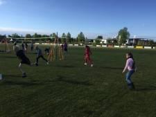 Leden van Forza volleyballen op het voetbalveld