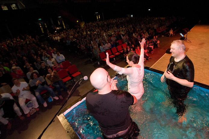 Kerkgangers laten zich dopen in een grote bak water op het podium van Mozaiek0318 in Veenendaal. Deze 'megakerk' overweegt zich ook in Apeldoorn te vestigen.