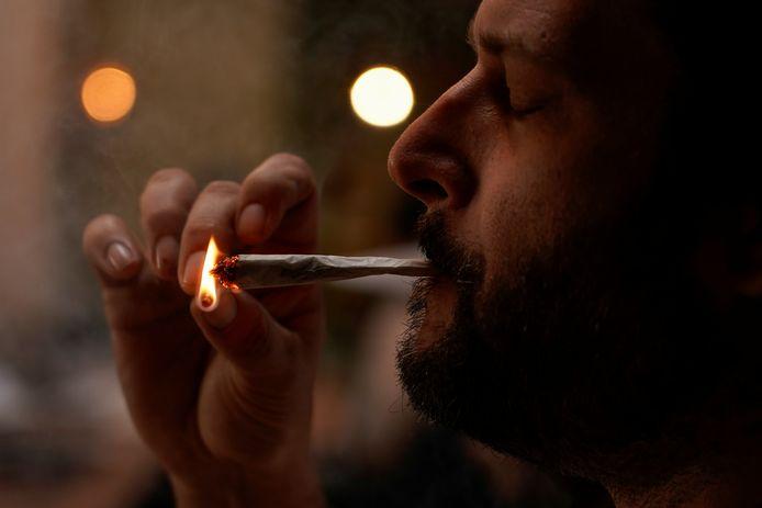 Een man steekt een joint op, archiefbeeld ter illustratie.