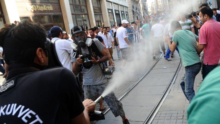 Een agent gebruikt traangas tegen betogers in Istanbul. Beeld afp