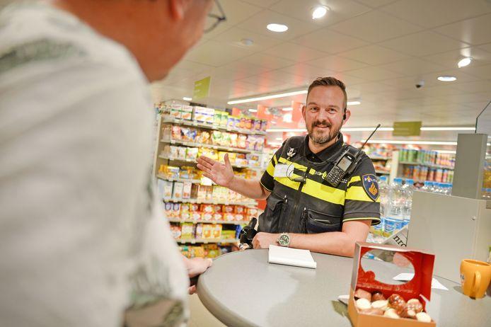 Wijkagent Jordy Scheggetman houdt spreekuur achter een staantafel in supermarkt Plus Blankhorst in Markelo