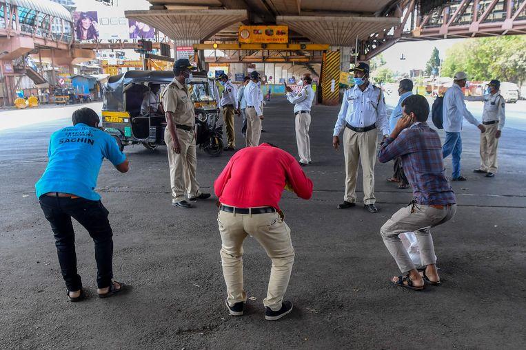 Politiemannen kijken toe hoe mensen als straf  push-ups doen tijdens de lockdown.   Beeld AFP