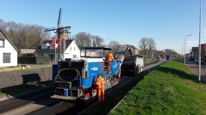 Een freesmachine haalt dinsdagmorgen de oude asfaltlaag van de Graafseweg door Alverna.