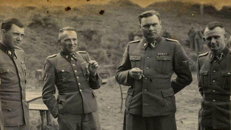 SS-officieren ontspannen in een buitenverblijf in de buurt van Auschwitz op een foto uit 1944. Van links naar rechts: dokter Josef Mengele, kampcommandant Rudolf Höss, Josef Kramer (kampcommandant van Birkenau) en een ongeïdentificeerd iemand.