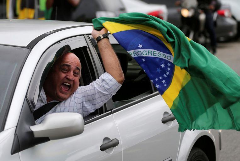 Een aanhanger van Jair Bolsonaro viert diens overwinning. Beeld REUTERS