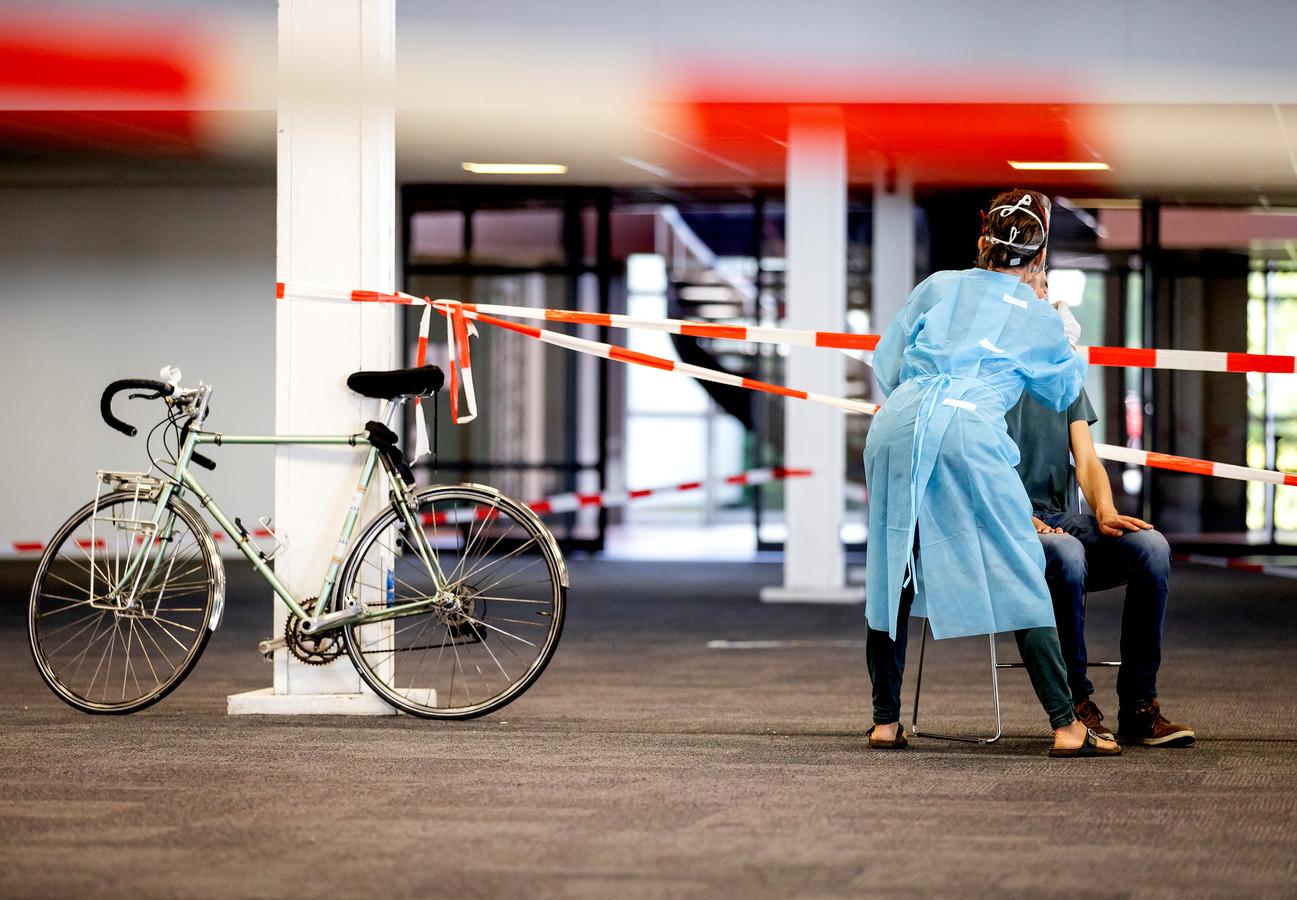 Medewerkers van de GGD Utrecht nemen coronatesten af in een teststraat in Houten. Iedereen die klachten heeft die lijken op symptomen van het coronavirus, kan zich laten testen.