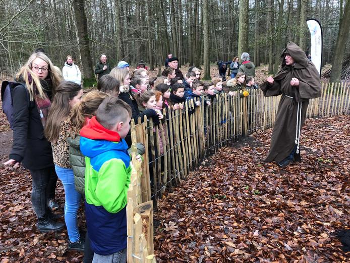 Kinderen luisteren naar de wijze woorden van 'pater Willibrordus' bij de Heksenboom in Bladel.