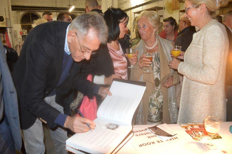 Auteur Erik De Schryver tekent zijn boek.