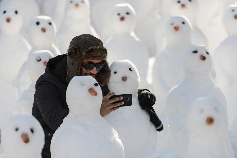 Kiezen tussen een selfie met sneeuwpop of Netflixen. Beeld AP