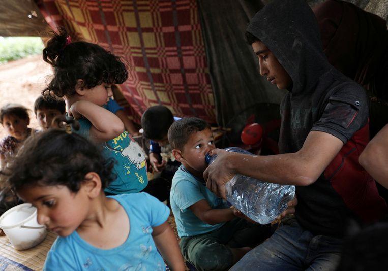 Een jongetje krijgt water van een ander familielid.