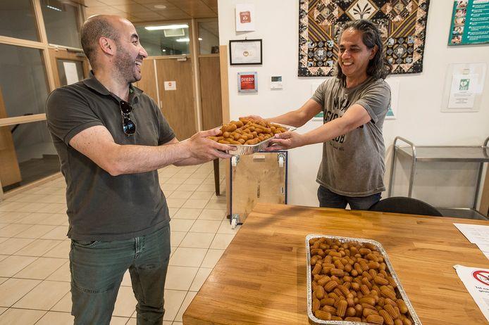 Younes Nahnahi (l) levert tulumba af aan de receptie van Huize Raffy voor het Suikerfeest.
