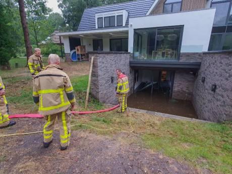 Onweersbuien trekken over Oost-Nederland, brandweer pompt volgelopen souterrain in Hoog Soeren leeg