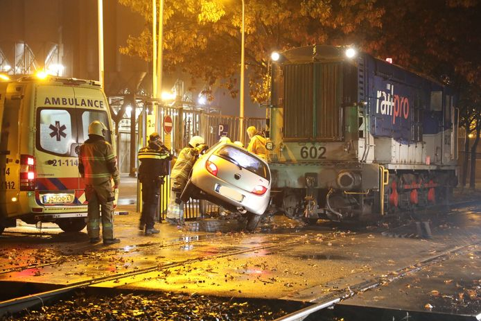 De auto staat ingeklemd tussen het hek en de trein