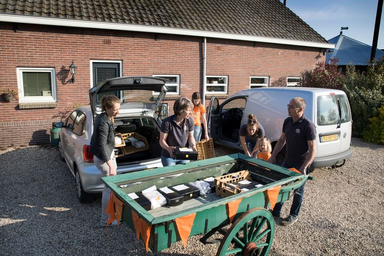 De familie van de Dorpswinkel heeft het gebak opgehaald en verdeelt het nu over de verschillende auto's en de handkar.  Beeld Werry Crone