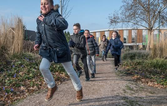 Kinderen lopen naar het beweegpark bij IKC De Dassburcht waar De Harlekijn in Cuijk in is gehuisvest.