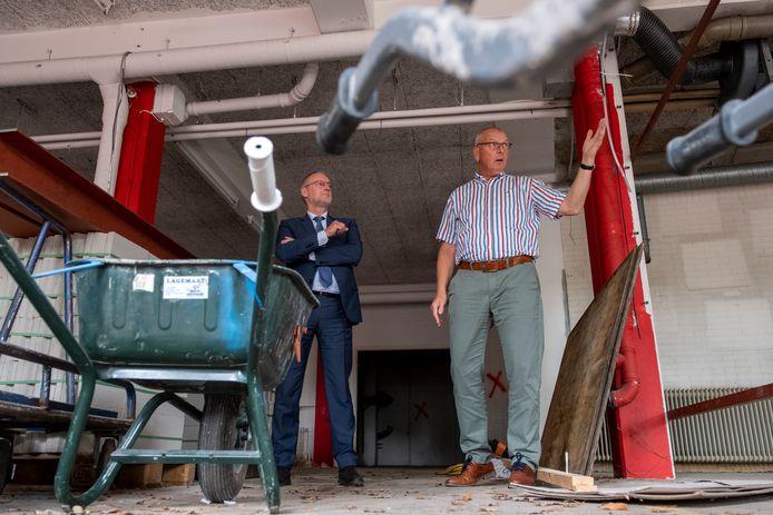 Projectleider Harrie de Graaf vertelt aan burgemeester Tom Horn over de verbouwing van het gemeentehuis in Epe. Zo wordt de voormalige brandweergarage een grote kantoorruimte.