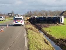 Vrachtwagen maakt schuiver en belandt op zijn kant in weiland