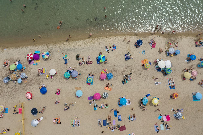 Zonnebadende Grieken op het strand van Epanomi, vlakbij Thessaloniki.  Griekenland zet op 15 juni de deuren weer open voor buitenlandse toeristen. Beeld EPA