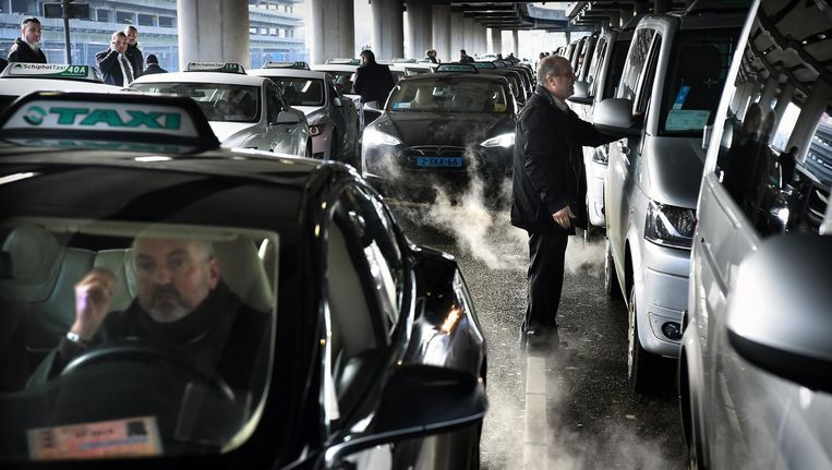 Taxi's op Schiphol. Een taxichauffeur die 'legaal' op Schiphol wil staan, moet hiervoor maandelijks honderden euro's betalen aan de luchthaven. Beeld Marcel van den Bergh / de Volkskrant