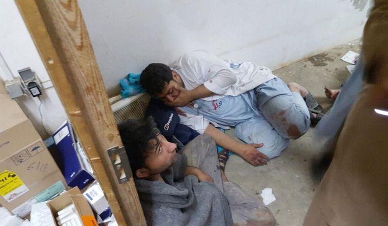 Medewerkers van het ziekenhuis zoeken dekking na het bombardement. Beeld AP