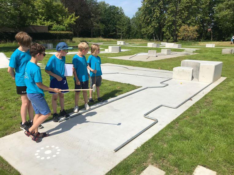 Leerlingen van basisschool De Springplank spelen golf met zelfgemaakte golfstokken.