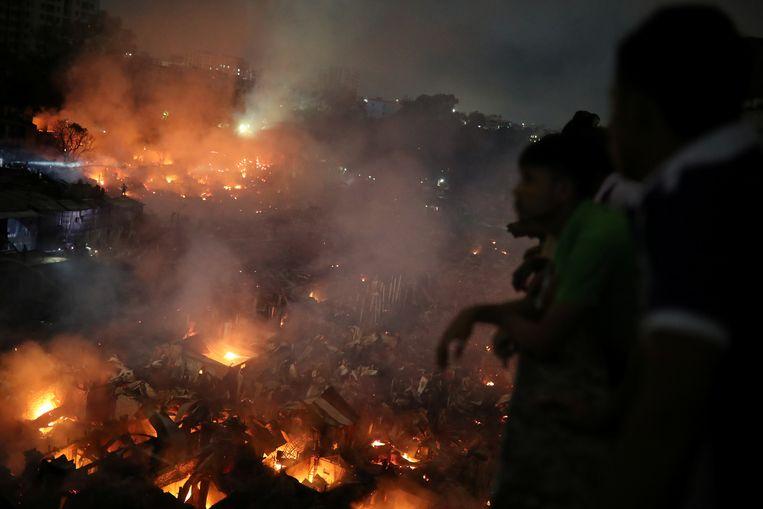 Mensen kijken vanop een hoger gelegen gebouw naar de vlammenzee.