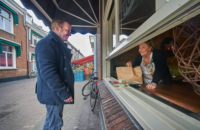 Bij restaurant Woodstock te Oss zijn ze overgegaan op afhaal via de kier van een raam. Op de foto klant Neal Bongers en Jacky van Raaij (van Woodstock)