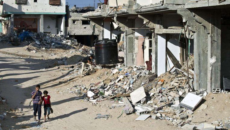 Twee Palestijnse kinderen lopen door een zwaar getroffen buurt in Gaza-stad. De luchten boven de stad zijn vrij van rook, sinds gisteravond. Beeld afp