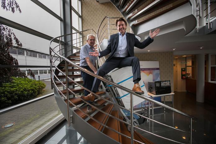 Rob Erkelens van Progest zit op een wasmachine die door Wim van den Broek met gemak een draaiende trap op wordt geleid dankzij de Stairmobil.