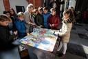 Bij de ganzenbordtafel in de kerk, helpt erfgoedadviseur Bibi Bodegom de kinderen tweetalig op weg.