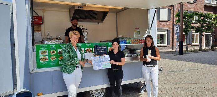 Wethouder Ursula Bekhuis reikte de voucher uit aan de eigenaren van de nieuwe foodtruck, die in Tubbergen op de markt staat.