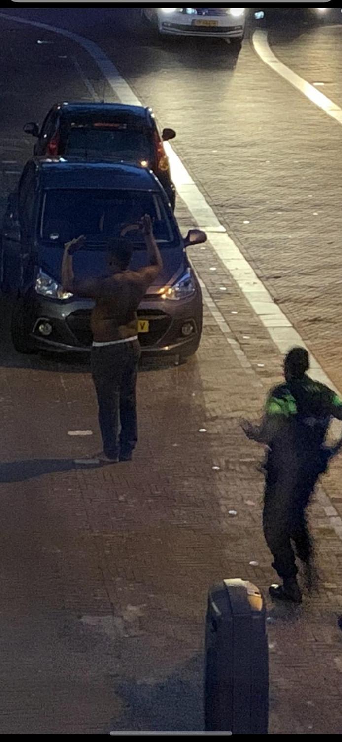 De aangehouden man, met de armen omhoog, in Huissen.