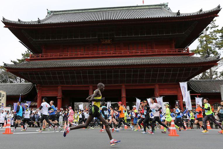Hardlopers passeren de Zojoji tempel tijdens de marathon in Tokio.  Beeld AP