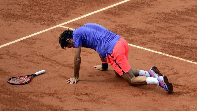 Roger Federer kruipt naar zijn racket nadat hij is gevallen tijdens zijn partij tegen Stan Wawrinka. Beeld EPA