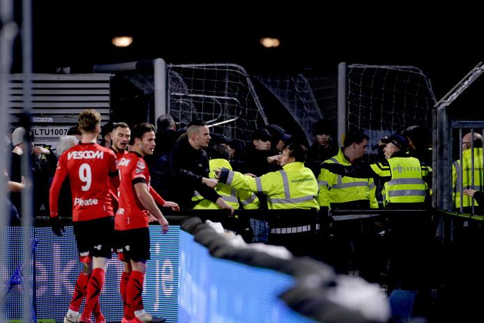 Spelers van Helmond Sport proberen supporters van hun club tot bedaren te brengen. Een groepje Helmondse fans zocht de confrontatie met Eindhovense fans.