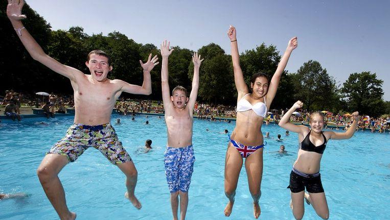 Bezoekers van zwembad De Dousberg in Limburg springen in het water. Beeld anp