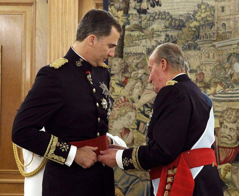 Juan Carlos geeft zijn zoon de sjerp die symboliseert dat hij de bevelhebber van de strijdkrachten is. Beeld REUTERS